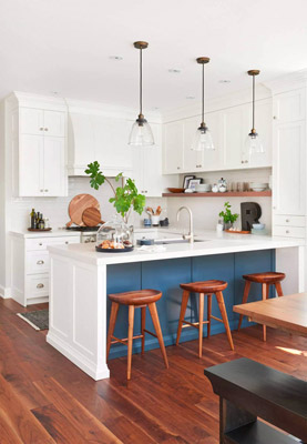 Spacious white kitchen design with blue accent wall and wood floors